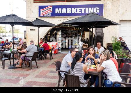 Cartagena Colombia El Laguito beach cafe restaurant tables umbrellas Hispanic resident residents man woman - Stock Photo