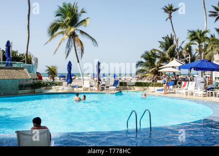 Cartagena Colombia El Laguito Hotel Dann hotel pool amenity Hispanic resident residents guests man swimming pool area lounging - Stock Photo