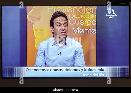 Cartagena Colombia TV television monitor screen flat screen medical program Spanish language osteoarthritis telemarketing Hispanic man - Stock Photo