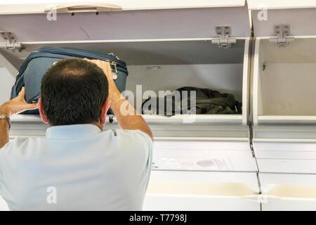 Cartagena Colombia Rafael Nunez International Airport CTG Avianca flight AV 34 onboard cabin Hispanic overhead luggage bin man storing bag - Stock Photo