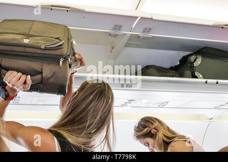 Cartagena Colombia Rafael Nunez International Airport CTG Avianca flight AV 34 onboard cabin Hispanic overhead luggage bin woman storing bag - Stock Photo