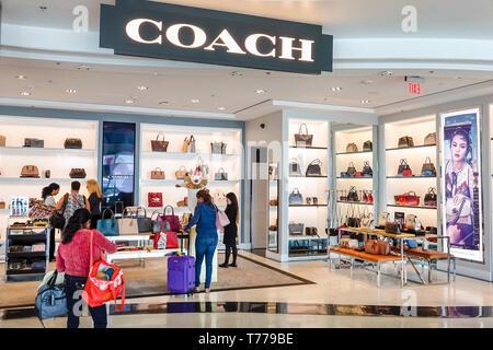 Miami Florida Miami International Airport MIA shopping Coach luxury brand handbags leather goods woman front entrance display sale - Stock Photo