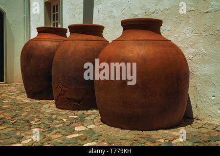 Close-up of large earthenware vessels over deserted floor and rough plaster wall at Campo Maior. A town with medieval influences in eastern Portugal. - Stock Photo