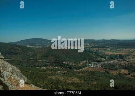 Mountainous landscape covered by trees and cultivated fields in a sunny day at Marvao. A medieval hamlet perched on a crag in Portugal. - Stock Photo