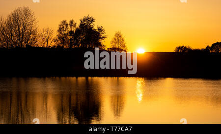 Near Tregaron, Ceredigion, Wales, UK. 04th May 2019  UK Weather: After a sunny, yet chilly day in the shade. The sun sets brightly over the countryside near Tregaron in mid Wales. © Ian Jones/Alamy Live News - Stock Photo