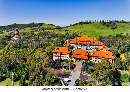 Chinese garden around Nan Tien Buddhist temple and high-rise pagoda tower on green hills near Wollongong in NSW, Australia. Elevated aerial view over  - Stock Photo