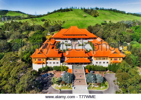 Massive main palace of Nan Tien Buddhist temple in the middle of green Chinese garden on hillside of Australian country near Wollongong. Aerial elevat - Stock Photo