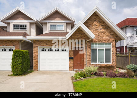 Half of residential duplex building with concrete drive way and lawn in front. - Stock Photo