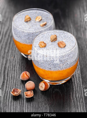 chia pudding in a glass on black wooden background - Stock Photo