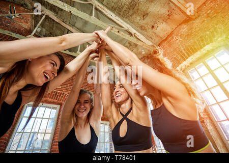 A group of beautiful girls give five in the fitness room. Concept of success, goal achievement. - Stock Photo