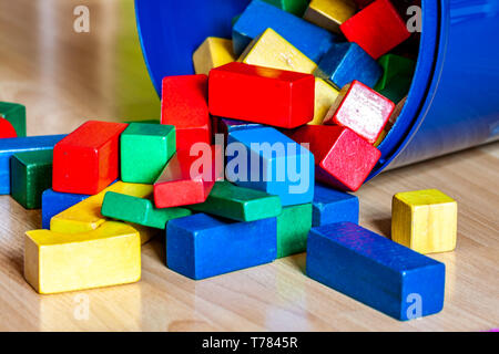 Colorful wooden building blocks on floor - Selective focus - Stock Photo