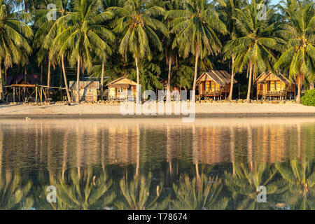 Beautiful bay with coconut palm trees and wooden bungalows which is reflected in seawater. Tropical sand beach, green palm leaf and sea water on the i - Stock Photo