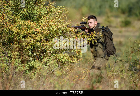 Hunter hold rifle. Man wear camouflage clothes nature background. Hunting permit. Hunting is brutal masculine hobby. Hunting equipment for professionals. Bearded serious hunter spend leisure hunting. - Stock Photo