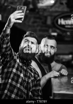 Man bearded hipster hold smartphone. Taking selfie concept. Send selfie to friends social networks. Man in bar drinking beer. Take selfie photo to remember great evening in pub. Online communication. - Stock Photo