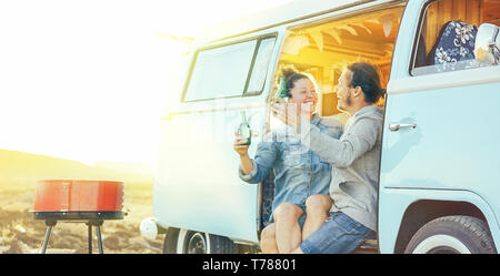 Travel couple having fun drinking beers sitting on their vintage camper mini van - Happy people with their pet enjoying barbecue at sunset - Stock Photo