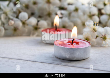 Closeup of red candles near the branches of white cherry blossoms. Burning candle - Stock Photo