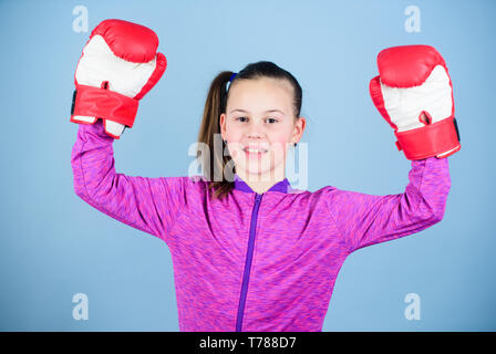 Enjoyment from sport. Female boxer. Sport upbringing. Boxing provide strict discipline. Girl cute boxer on blue background. Contrary to stereotype. Boxer child in boxing gloves. Confident teen. - Stock Photo