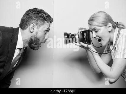 Emotions through photos. Businessman posing in front of female photographer. Pretty woman using professional camera. Photographer shooting male model in studio. Fashion shooting in photo studio. - Stock Photo
