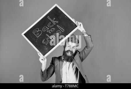Teacher with tousled hair cheerful about school year beginning. Keep working and be kind to people. Stay positive. Teacher bearded man holds blackboard with inscription back to school blue background. - Stock Photo