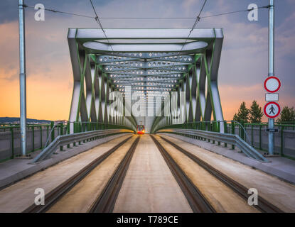 Perspective View of Old Bridge with Approaching Tram in Bratislava, Slovakia at Sunset - Stock Photo