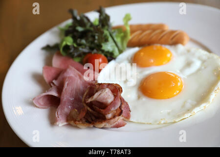 Breakfast set with fried eggs, bacon, sausages, beans, toasts, fresh salad and fruit on wood table - Stock Photo