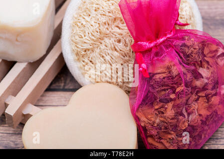 Wooden Soap Holder with a Heart shaped Goat milk Soap, Natural loofah sponge and dried roses on wooden background. - Stock Photo