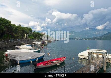 A view across Lenno harbour across Lake Como towards Bellagio in the distance with mountains beyond, under a moody grey sky - Stock Photo