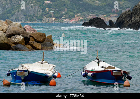 In Cinque Terre, Italy, looking past two small boats on Vernazza harbour to Monterosso beyond - Stock Photo