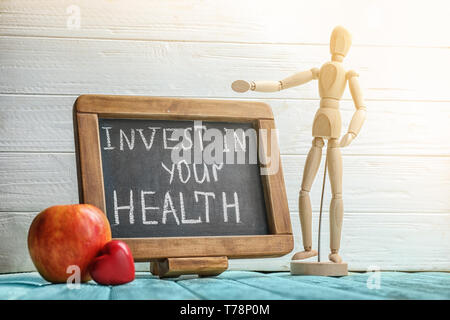 Blackboard with phrase 'Invest in your health' on wooden table - Stock Photo