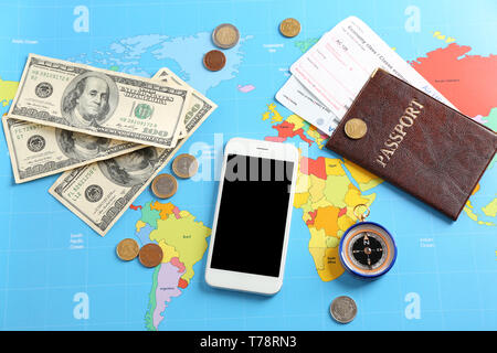 Mobile phone, passport and money on world map. Travel concept - Stock Photo