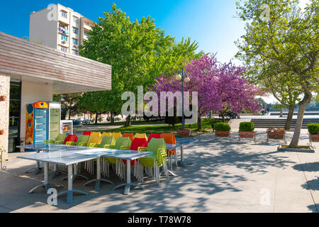 Empty cafe in the early morning, city park at spring time - Stock Photo