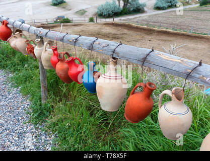 Multicolored clay pots of desires hang tied on a wooden crossbar in Cappadocia against the backdrop of green grass and sand gardens. - Stock Photo