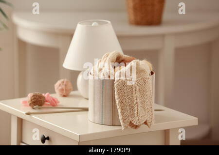 Box with knitting balls and clothes on table - Stock Photo