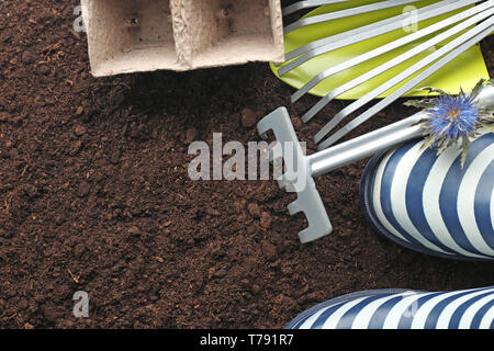 Gardening tools and rubber boots on ground - Stock Photo