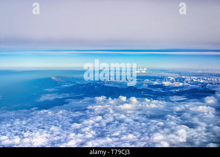 Aerial view of monsoon clouds over a mountain range in India. The snow covered peaks of Shivalik/Dhauladhar range can be seen on top right. - Stock Photo