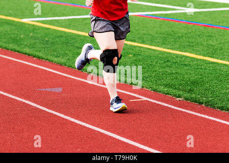 A runner is practicing on a red track while wearing a large black knee brace. - Stock Photo
