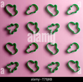 many cookie cutters isolated on the pink background.top view. preparation of cake - Stock Photo