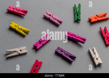 Group of wooden colorful clothespins on gray background. top view photo. - Stock Photo
