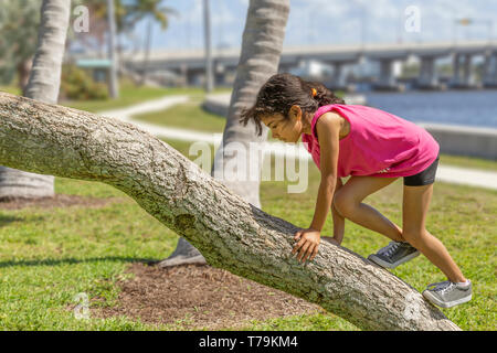 The young schoolgirl makes her way up the trunk. A popular summertime park on the waterfront is where she enjoys exploring the play area. - Stock Photo