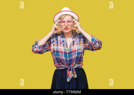 Headache or confusion. Portrait of frowning stylish mature woman in casual style with hat and eyeglasses standing holding her head with head pain. ind - Stock Photo