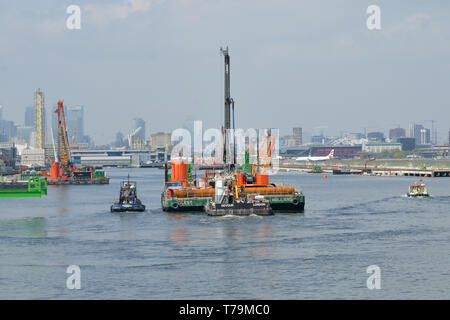 Tugs moving an engineering barge in the King George V Dock, London, as part of the London City Airport CADP expansion works - Stock Photo