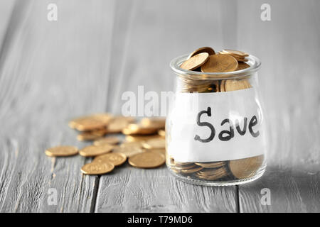 Coins in glass jar with text SAVE on table. Concept of savings - Stock Photo