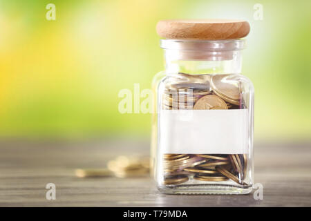 Glass jar with coins and label on table against blurred background. Concept of savings - Stock Photo