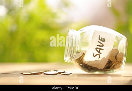 Coins in glass jar with text SAVE on table against blurred background. Concept of savings - Stock Photo