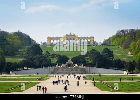 Austria tourism, view of tourists walking through the formal gardens of the Schloss Schönbrunn palace in Vienna, Austria. - Stock Photo