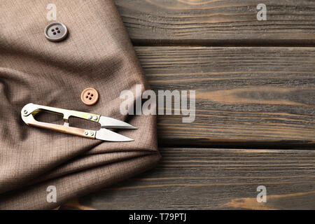 Fabric and sewing accessories on wooden background - Stock Photo