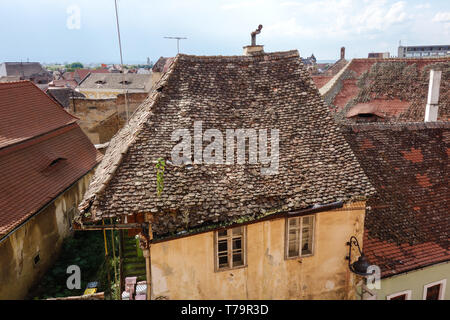 Weathered rooftop of an old house with an unique chimney in Sibiu (Hermannstadt), Romania - Stock Photo