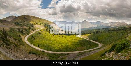 Wide panorama of the view over a large horseshoe bend on Cottonwood pass in Colorado USA with cars racing towards the summit - Stock Photo