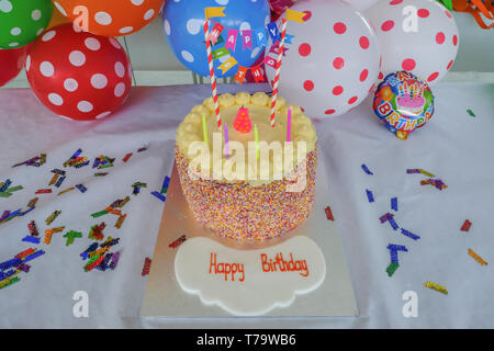 Children's Birthday cake with candles set in front of colourful spotty ballons. Ready for a party with Happy Birthday written in the foreground. - Stock Photo