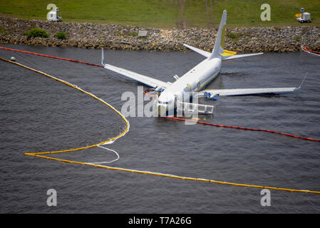 190504-N-SR482-002  JACKSONVILLE, Fla. (May 4, 2019) Containment and absorbent booms surround a Boeing 737 aircraft in the St. Johns River after the aircraft slid off the runway at Naval Air Station Jacksonville, May 3, 2019. All 143 passengers aboard the flight from Naval Station Guantanamo Bay, Cuba were rescued. National Transportation Safety Board officials are on scene leading the investigation. (U.S. Navy photo by Mass Communication Specialist 3rd Class Thomas A. Higgins/Released) - Stock Photo